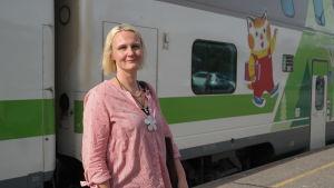 Linnea Henriksson står bredvid ett tåg med en bild av en katt som visar att här finns barnvagn