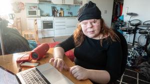 En kvinna sitter hemma framför en dator. Till höger, från kvinnan sätt, finns en orange högtalare.