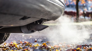 auto ja pakokaasu syksyisessä maisemassa
