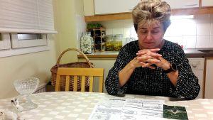 En dam sitter vid ett köksbord med blicken på en räkning som ligger på bordet.