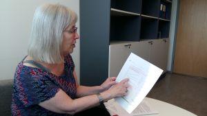 En kvinna pekar på ett vitt papper med grafer och text.