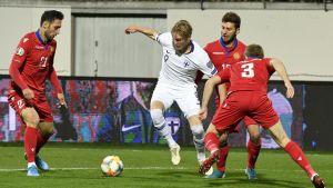 Fredrik Jensen dribblar mellan tre armeniska spelare.