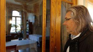 Mikael Lindfelt, en man med glasögon och axellångt grånande hår, tittar in genom ett fönster till en sal i ett 1800-talshus.