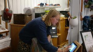 Tone Leganger vid datorn i sin garnaffär