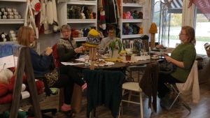 Fyra damer sitter runt ett bord och stickar