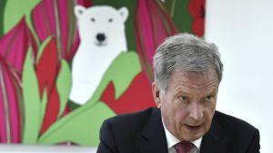 President Niinistö till höger. I bakgrunden ett konstverk som föreställer en isbjörn i ett buskage.