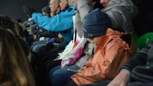 En pojke sitter och tittar på sin telefon på en läktare där alla vuxna följer med matchen.