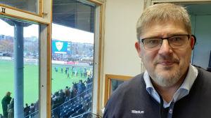 Rainer Svens, en man grånande hår, grånande skägg och glasögon. I bakgrunden firar fotbollsspelare nere på planen att de vunnit.
