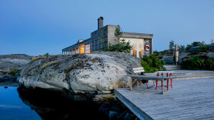kalliolla veden äärellä näkyvä talo.