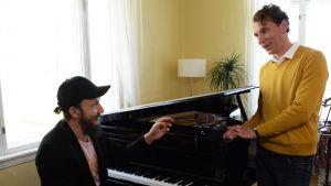 Muusikko Samuli Putro puhuu flyygelin ääressä kirjailija Juha Itkoselle