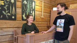 Vilma Pellinen ja Janne Uusitalo kotitalossaan. Vilma istuu vanhan pulpetin takana ja seinillä roikkuu kasviskuvastoja.