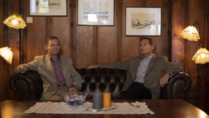 två män sitter i en soffa