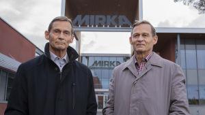 två män framför ingång till industri