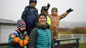 Anna Törnqvist omgiven av dagisbarn i färggranna kläder utomhus.
