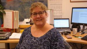 Viveca Smeds-Aalto sitter i närbild med datorskärmar i bakgrunden