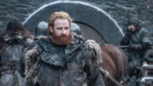 Kristofer Hivju somTormund Giantsbane i Game of thrones. Vinter, i bakgrunden syns häst och kärra och mur.