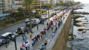 Människor står vid en gata i Beirut och formar kedja genom att hålla varandra i händerna.