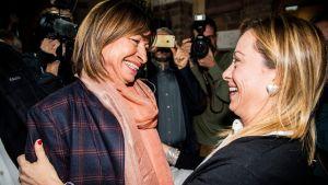 Två kvinnor ger varandra en kram under firandet av valsegern.