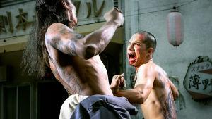Kaksi gangsteria tappelee ilman paitaa kauhuelokuvassa Suuri yakuzasota (Yakuza Apocalypse)