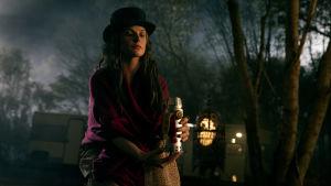 Rose the Hat (Rebecca Ferguson) sitter på marken med en behhållare av människogas i handen.
