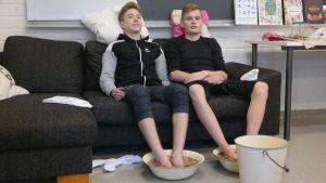 Pojkarna Juhana Virkkunen och Ludvig Fagerlund sitter med fötterna i fotbad