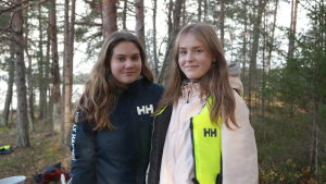 Eleverna Elin Kari och Frida Hausen står på stranden med träd i bakgrunden