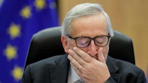 Jean-Claude Juncker silmät kiinni ja käsi suunsa edessä EU-lippu taustallaan.