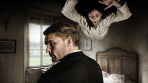 Mies katsoo olkansa yli kameraan, katossa vaalepukuinen riivattu nainen.