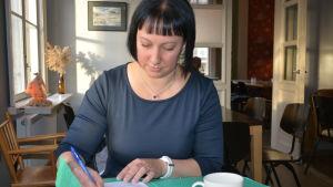 Kvinna antecknar på café.