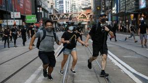 Många svartklädda demonstranter bär ansiktsmasker trots att de har förbjudits av polisen