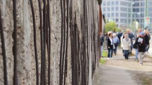 På sidan i bilden löper en cementmur där armeringsjärnen sticker fram. Längre bort i bakgrunden ser man många människor som finns vid muren och tittar på den.