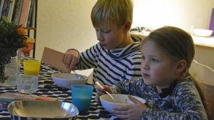 Två barn äter fisksoppa vid matbordet.