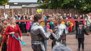 Kaksi haarniskoihin pukeutunutta miestä pitävät toisiaan käsistä hymyillen. Taustalla muita ihmisiä ja yleisöä.