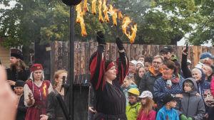 Nainen kantaa käsissään palavia soihtuja pukeutuneena keskiaikaiseen asuun. Taustalla muita esiintyjiä ja yleisöä.