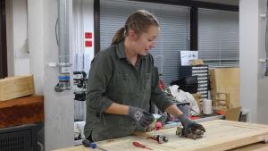 Camilla Wennström håller på och restaurerar en gammal dörr vid en hyvelbänk