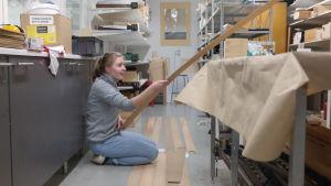 Kristin Wikström sitter på golver och håller i en lång bräda till den sup bräda hon håller på att tillverka
