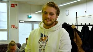 en ung man i vit tröja bland andra studenter
