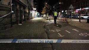 Polistejp avspärrar gata i Malmö, polis och vapenhund genomsöker området.