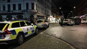 Avspärrad gata med flera polisbilar.