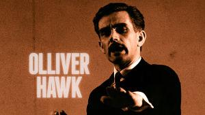 Mies puvussa katsoo kameran sormet edessä. Taustalla teksti Olliver Hawk.