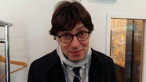 En man med pillimarisk min, svart hår och tjockbågade glasögon tittar in i kameran.
