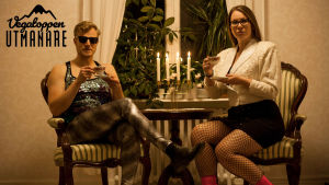 Man och kvinna sitter vid rund bord och dricker ur gamla kaffekoppar i porslin.