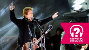 Chad Kroeger står med uppsträckta händer, har en elgitarr kring halsen och sjunger i en mikrofon.
