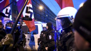 Demonstranter med nazistflaggor och poliser.