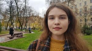 En allvarlig ung kvinna med brunt långt hår i en rutig kappa och en gul polotröja tittar in i kameran. I bakgrunden ser man en park med träd utan löv, men med grönt gräs.