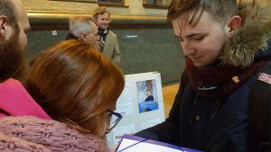 En ung man i en blå jacka med pälsliknande krage och en röd halsduk tittar ner på ett papper och framför honom står två personer med bakhuvudena mot kameran framåtlutade mot papperet den unga mannen håller i.