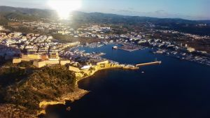Bild över en bukt i Ibiza med solen i bakgrunden.