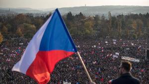 Man står med ryggen mot kameran och håller i tjeckisk flagga.