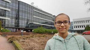 En kvinna med glasögon står framför en campus byggnad