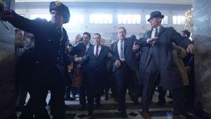 Frank Sheeran (Robert de Niro) eskorterar Jimmy Hoffa (Al Pacino) till domstolen, de är omringande av poliser och män.